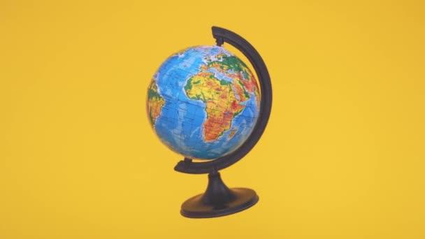 Létá s nulovou gravitací na žlutém pozadí. Škola zeměpisu. Ekologický koncept. Den Země
