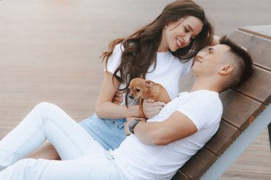 Young happy couple on walk with small dog. Lifestyle Concept