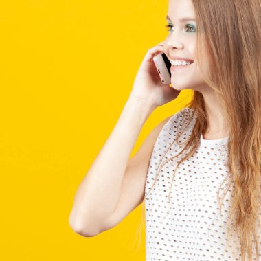 Cheerful young girl talking on phone and smiling. Emotions, communication and technology