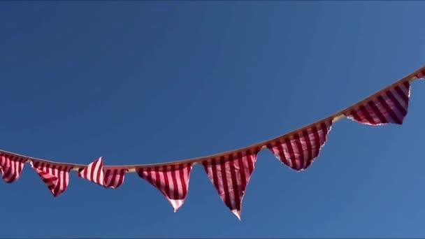 Piros-fehér csíkos háromszög lobogó zászló sármány fúj a szél