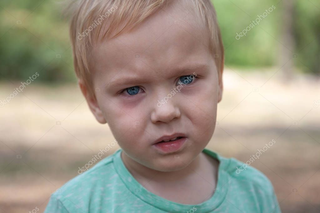 Close up portrait of cute caucasian baby boy with serious expression in blue eyes. Moment of tears. Blonde hair. Outdoors, copy space. Park background.