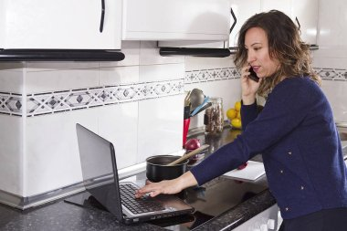 A woman cooking and using a laptop