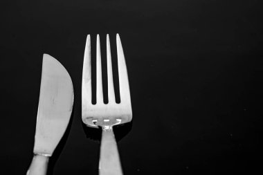head of knife and fork on black background