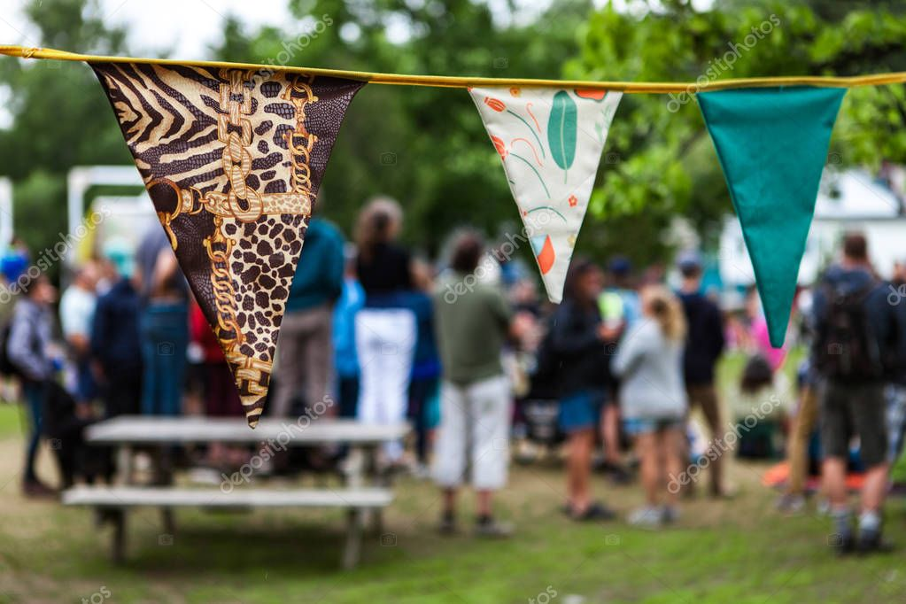 3 homemade pennants in front of a group of people enjoying the summer in the park