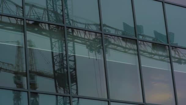 Svislá část nad okny odrážející stacionární jeřáb