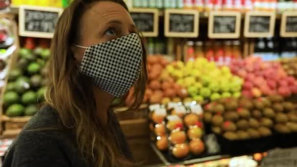Žena s vozíkem v obchodě s potravinami s maskou