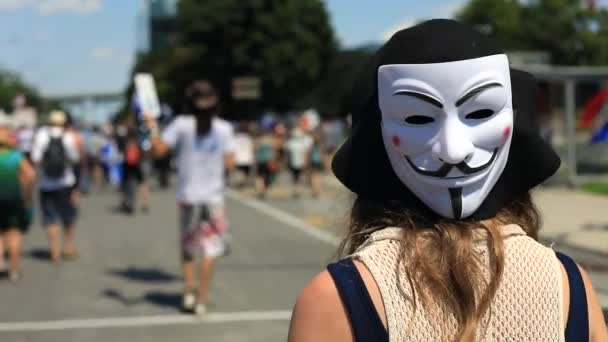 Woman with anonymous mask walking in protest