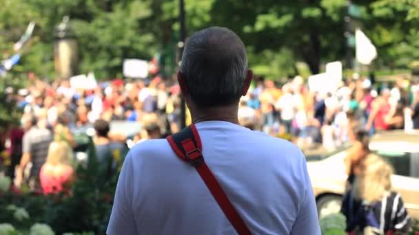 Senior man standing away looking at crowd