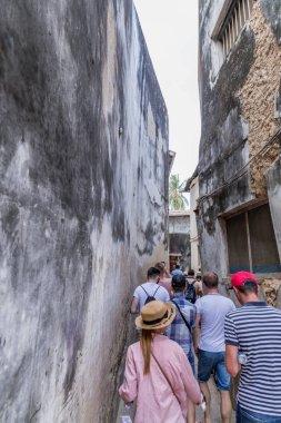 2018.02.24, Stone Town, Zanzibar, Tanzania. Travel around Africa. Tourists and locals on the narrow street of Stone Town.