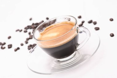 Hot black coffee in a clear glass on a white background with coffee beans.