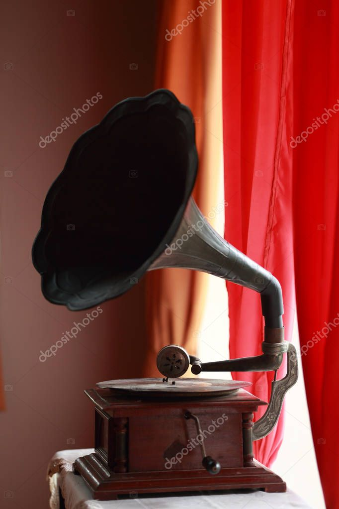Ancient Turntables Placed by the window with red curtains hanging.