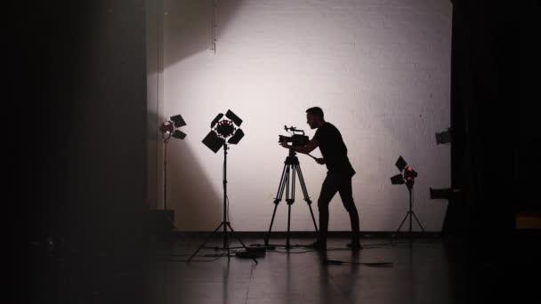 Silhouette of Cameraman Working Behind the Scenes in Film Studio