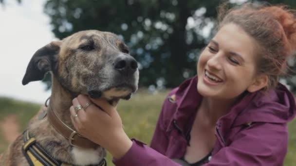 Beautiful Happy Young Woman Stroking her Loving  Loyal Pet Dog in Park
