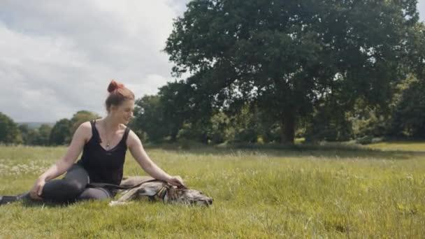 Giovane donna che si distende con il cane nel parco / verde prato