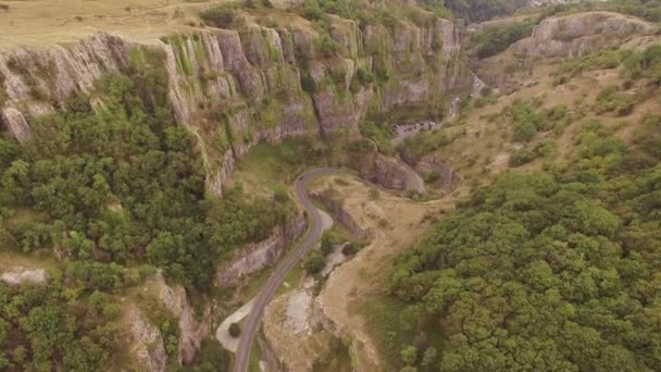 Cars driving on winding scenic road in beautiful valley, aerial drone shot