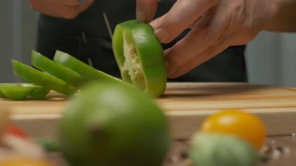 Professioneller Koch bereitet und schneidet grüne Paprika. Zeitlupe in Großaufnahme
