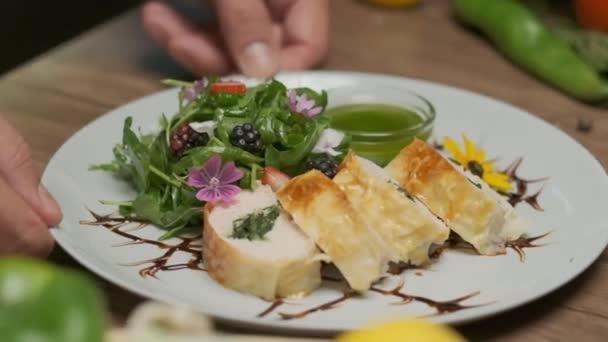 Tisch mit frischem Gemüse, Gewürzen und Hühnerbrötchen mit Spinat schön serviert auf einem Teller mit Gemüse, Blumenschmuck und grünem Öl