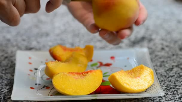 Cutting and separating the peach from the stone, slices of ripe juicy peach on a plate, video, soft focus