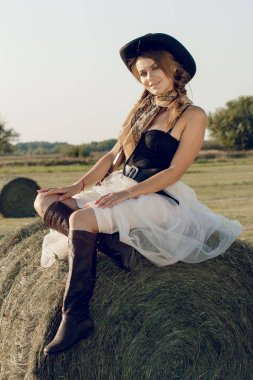 A young woman dressed as a cowgirl stands in a farmer's crop field corn at sunset and rests at a haystack