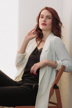 Beautiful redhear woman white jacket, high heels, and black shirt sitting the balcone