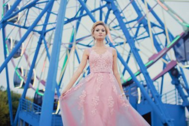Young beautiful woman in long pink evening dress walking path in park. Fashion style portrait of gorgeous beautiful girl outdoors near the Ferris wheel