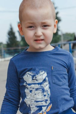 Portrait of cute smiling little boy in blue shirt, outdoor shot