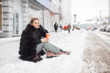 girl sitting on a snow in the city on curb covered with snow. Lifestyle. winter mood, coffee cup, mink fur clothing.