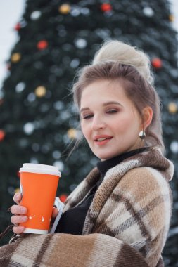 winter holidays, hot drinks, woolen plaid and people - happy young woman with coffee over christmas lights outdoors