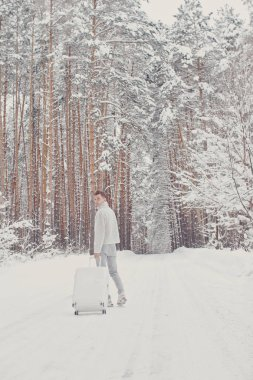 Portrait of young fashionable man in white clothes walking on snow holding suitcase and go pathway pine forest. Winter vacation travel concept. Outdoors in winter. Ski resort, mounting skiing resort