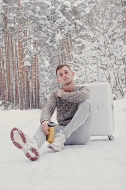 Portrait of young fashionable man in white clothes sitting on snow holding suitcase and go pathway pine forest. Winter vacation travel concept. Outdoors in winter. Ski resort, mounting skiing resort
