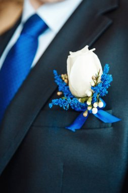 White rose and blue delphinium boutonniere flower on groom's wedding coat with blue tie