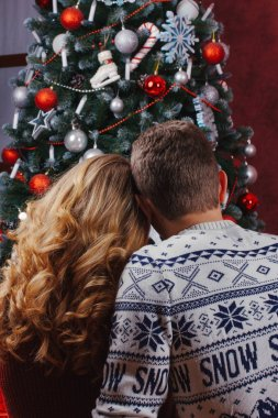 Couple in love sitting next to a Christmas tree, wearing warm sweaters, hugging and looking away from the camera towards the tree.