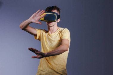 technology, gaming, entertainment and people concept - young man with virtual reality headset or 3d glasses. Studio shot, gray background.