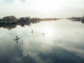Fotografie Blick von oben auf Touristen am See mit SUP-Boards. Wunderschönes klares Wasser mit Menschen, die auf Surfbrettern schwimmen. Seelandschaft mit Ruderern auf Brettern am Horizont
