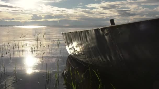 Boat on the shore of the lake during sunset