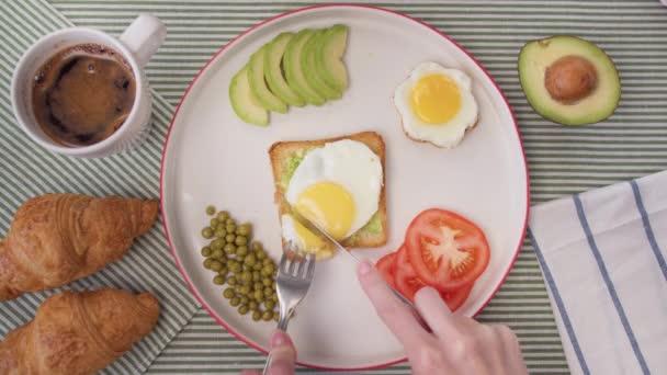 Top view női kéz vágott pirítóst avokádóval és tojással. Reggeli otthon, frissítő kávé és pirított pirítós avokádóval és tojással