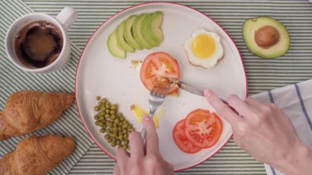 Top view gyorsított lövés női kéz vágott pirítóst avokádó és tojás. Gyors reggeli otthon, kávé és pirított pirítós tojással