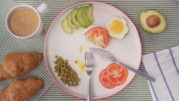Top view Reggeli asztal, női kezek isznak egy csésze kávét croissant-nal. Házi ebéd szendvics és avokádó, paradicsom, borsó.