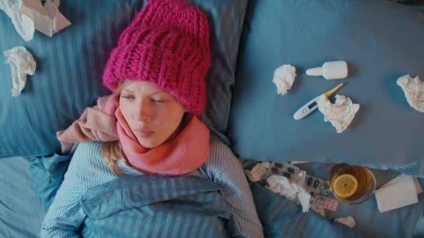 Kranke junge Frau liegt im Bett. Schöne Teenagerin mit pinkfarbener Strickmütze und warmem Schal am Hals hustet und pustet ihre Nase an Servietten. Grippe und andere Atemwegserkrankungen. Saisonbedingte Krankheit