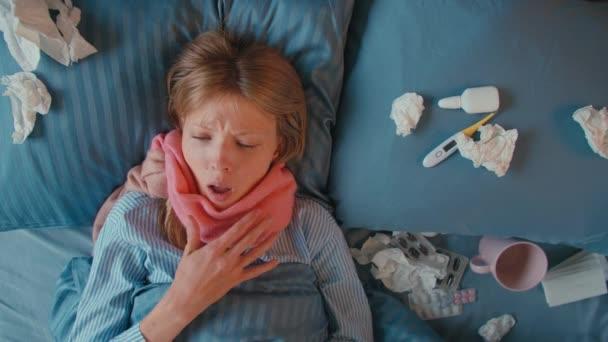 Schöne 25er Frau mit Halstuch hustet und pustet ihre Nase in Serviette, Frau hüllt sich mit einer warmen Decke über den Kopf. Grippe und andere Atemwegserkrankungen. Ansicht von oben