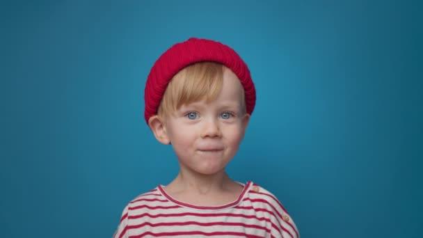 pohledný modrooký chlapec v červeném klobouku na modrém pozadí se směje