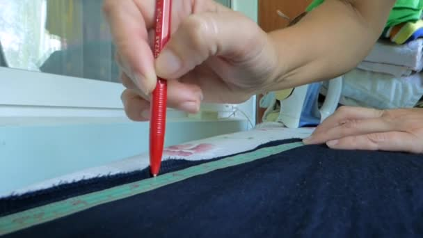 the tailor makes a mark on the fabric