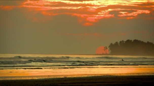 Szűz érintetlen karibi tengerparton naplementekor. Golden és red sun ragyogó fény alatt homokos strandok alkotják egy félelmetes trópusi táj. Hajnalban látványos színes háttérrel.