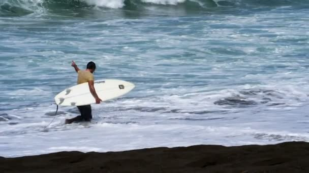 Young surfer walking on the beach with his surfboard under his arm.Surfer ready to surf the waves in the Caribbean Sea.Water sports videos in super slow motion.