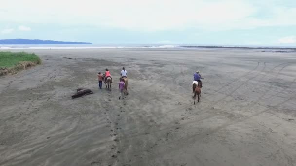 Family riding horses on the seashore aerial drone view.Horse ride on the white sands of the beach.Riding on horseback by the sea.