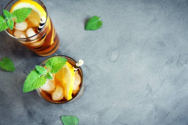 Iced Tea with lemon, mint and ice cubes over gray concrete background, copy space. Iced cold summer drink.