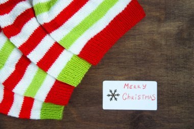 Colorful christmas red, white and green knitted patterns of Santa claus helper hat, natural wool, handmade knitted, with paper christmas cards and snowflakes on brown wooden background. Top view