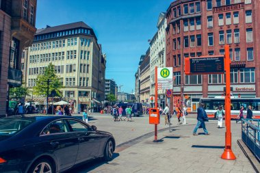 Street with people and cars near metro station Rathausmarkt and town hall Rathauson the market square, near lake Alster Binnenalster in Altstadt quarter, Hamburg Germany