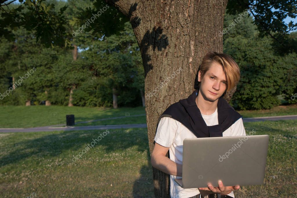 Young man with laptop  working in the park near office building