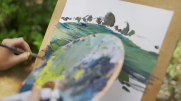 Künstlerin im Park malt eine Landschaft mit Ölfarben einen kleinen alten Teich 4k